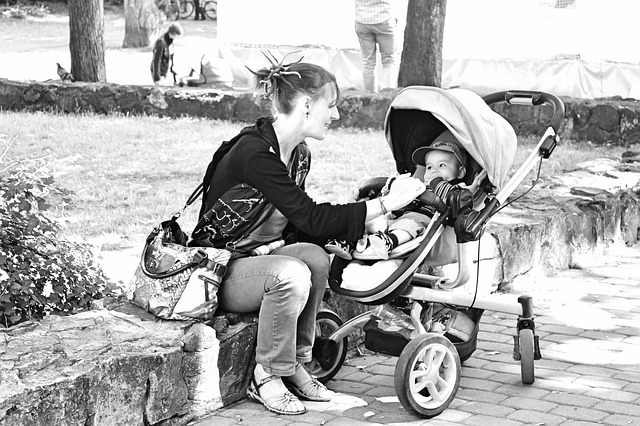 matka s kočárkem v parku