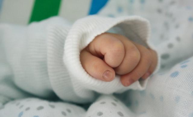 Ruka bábätka v bielom tričku na bodkovanom paplóne