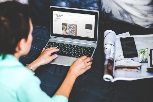 Žena ležiaca na posteli, ktorá pracuje na notebooku.jpg